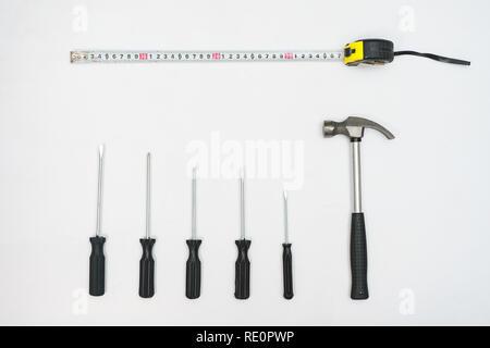 Ansicht von oben aus Hammer, Schraubendreher und Maßband auf weißem Hintergrund - Stockfoto