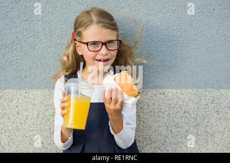 Süße blonde Mädchen im Alter von 7 Jahren ein Sandwich essen und trinken Orangensaft - Stockfoto
