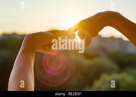 Hände zeigen Geste der Finger zusammen, Symbol der Freundschaft und Beziehung. Hintergrund Abend Sonnenuntergang, Stadt Silhouette - Stockfoto