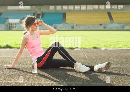 Schöne Mädchen im Teenageralter Ausruhen nach Training im Stadion, Mädchen setzte sich zu entspannen, Trinkwasser - Stockfoto
