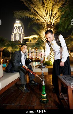 Mann Rauchen einer Wasserpfeife, Shisha, am Pool am Abend, das Palace Hotel, Altstadt, Dubai, Vereinigte Arabische Emirate, Naher Osten - Stockfoto