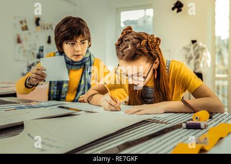 Kreative talentierte Mädchen mit schönen Frisur Zeichnung Skizzen Stockfoto