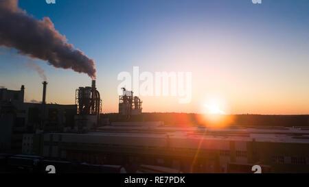 Sonnenaufgang über der Fabrik. Der Rauch kommt aus den Leitungen in der Morgendämmerung. - Stockfoto