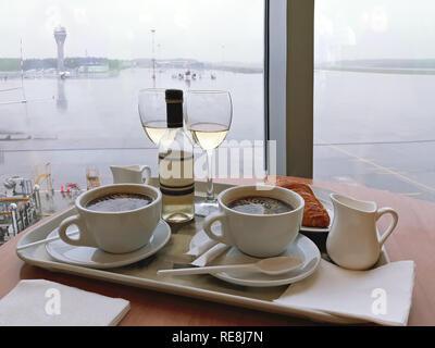 Zwei Tassen Kaffee und eine Flasche mit zwei Gläser Wein auf einem Tablett gegen die Landebahn Hintergrund. - Stockfoto