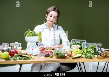 Frau Ernährungsberater in der medizinischen einheitliche Arbeiten auf einer Diät plan Sitzung mit verschiedenen gesunden Zutaten in der Green Office - Stockfoto