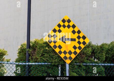 Gelbes Schild mit kleinen Plätzen und zurück Links schwarz Richtungspfeil - Stockfoto