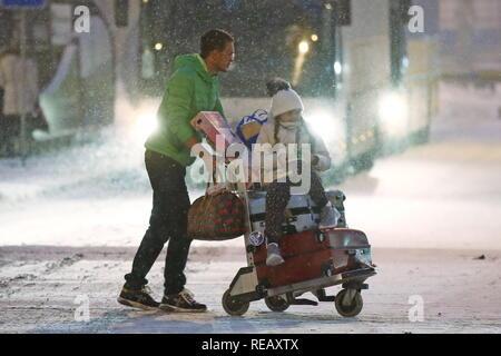 Moskau, Russland. Jan, 2019 21. Moskau, Russland - Januar 21, 2019: ein Mann treibt ein Gepäckwagen in einem schneefall am internationalen Flughafen Scheremetjewo. Valery Sharifulin/TASS Credit: ITAR-TASS News Agentur/Alamy leben Nachrichten - Stockfoto