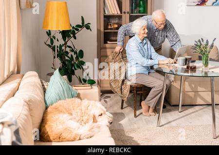 In voller Länge Porträt des modernen senior Paar mit Laptop am Tisch zu Hause sitzen mit Hund im Vordergrund, Kopie Raum - Stockfoto