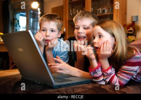 Geschwister, 7, 11, 13 Jahre alt, mit Laptop im Wohnzimmer, spielen ein lernspiel Quiz - Stockfoto