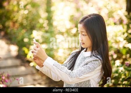 Schönen kleinen asiatischen Mädchen mit langen Haaren ein selfie gegen Blume Hintergrund mit Handy - Stockfoto