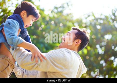 Asiatische Vater Spaß heben Sohn külschrank im Park. - Stockfoto