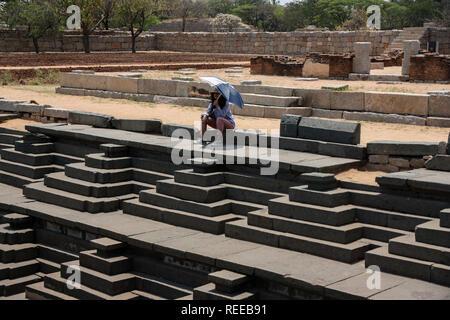 Weibliche indische Touristen mit einem Regenschirm auf das öffentliche Bad und das Royal enclosure Schritt Wasser gut in Hampi, Karnataka, Indien sitzen.