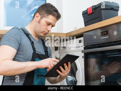 Heimwerker, Inspektion der Waschmaschine in der Küche. - Stockfoto
