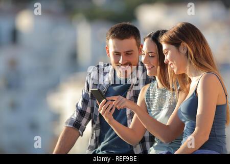 Drei glückliche Freunde mit einem smart phone in einer Stadt bei Sonnenuntergang - Stockfoto
