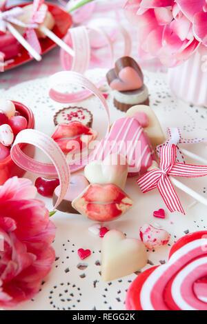 Leckere Süßigkeiten in Form eines Herzens und frisches rosa Tulpen - Stockfoto