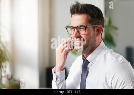 Close-up Portraitfotos der stattlichen Geschäftsmann mit Hemd und Krawatte im Büro sitzt und spricht mit jemand auf seinem Handy. - Stockfoto