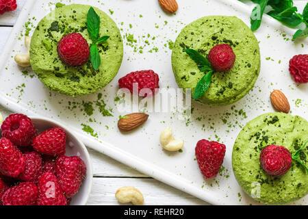 Hausgemachte raw Matcha Pulver Kuchen mit frischen Himbeeren, Minze, Muttern. Gesunde vegane Ernährung Konzept. top View - Stockfoto