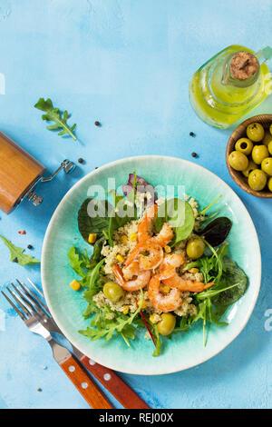 Diätmenü, veganes Essen. Gesunde Salate mit Quinoa, Rucola, Garnelen und Oliven auf einem blauen Tisch aus Stein. Ansicht von oben flach Hintergrund. Kopieren Sie Platz.
