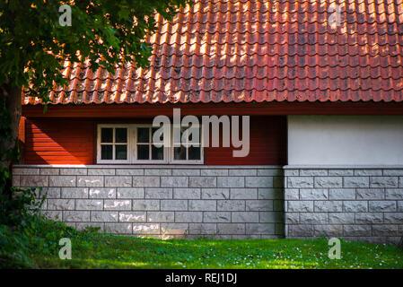 Sonnenstrahlen fallen durch die Bäume auf den schönen, kleinen brick House oder Scheune in der Landschaft neben Wald. Häuschen mit rotem Dach. - Stockfoto