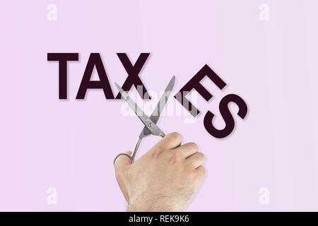 Von Hand mit der Schere schneiden das Wort Steuern - Stockfoto