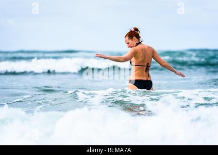 Frau genießen das Meer und die Wellen des Atlantik. Reife, mittlere Alter, junge attraktive Frau im Badeanzug Bikini läuft im Ozean Meer, Verscherzen - Stockfoto