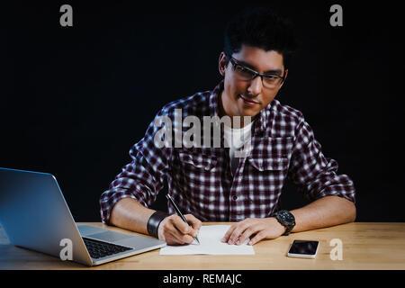 Programmierer im Büro am Computer arbeitet und schreibt auf ein Blatt Papier - Stockfoto