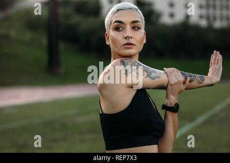 Sportlerin mit Tattoo auf dem Arm zu tun Stretching Übungen in einer Masse. Porträt einer Frau, die in der Fitness Kleidung, Warm-up Übungen. - Stockfoto