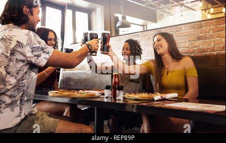 Multi-ethnischen Gruppe von Menschen toasten alkoholfreie Getränke in einem Café. Männer und Frauen sitzen in einem Restaurant das Toasten von Getränken. - Stockfoto