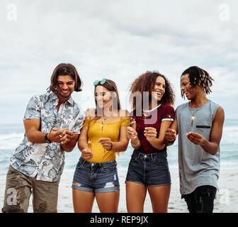 Gruppe von multi-ethnischen Freunde genießen am Strand mit Wunderkerzen. Junge Männer und Frauen Spaß mit Feuerwerk am Meer. - Stockfoto