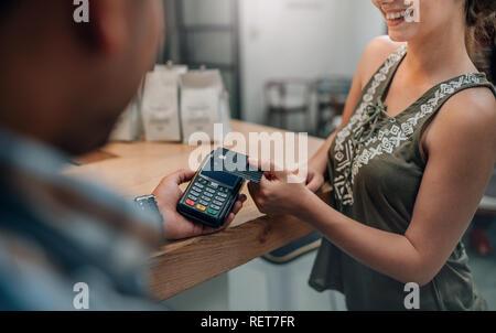 Kellner accpeting Kreditkarte durch das kontaktlose Bezahlen. Kunden die Zahlung durch Kreditkarte NFC-Technik - Stockfoto