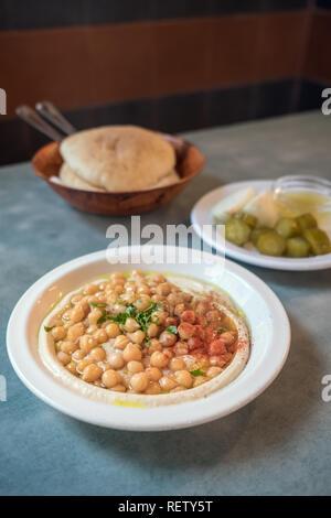 In einem israelischen Mittagessen im Café in Tel Aviv, Israel. Cremigen Hummus mit ganzen cheakpeas Nahaufnahme, Haufen von Pitas und Pickles auf dem Hintergrund - Stockfoto