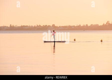 Syrakus, Italien / Dezember 2018: Stand up Surf Mädchen mit Paddeln in einem Sonnenuntergang ozean meer - Stockfoto