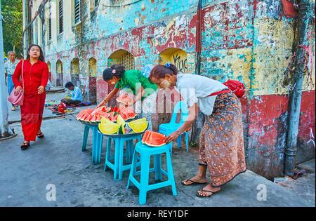 YANGON, MYANMAR - Februar 17, 2018: Spontane Handel in Chinatown - Frauen verkaufen Scheiben rote und gelbe Wassermelonen aus den Fächern, stehend auf dem - Stockfoto