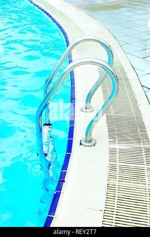 Leeren Swimmingpool mit blauem Wasser und mit Treppe aus Edelstahl im Aquapark Nahaufnahme - Stockfoto