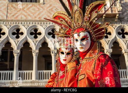 Karneval in Venedig. Zwei wunderschöne venezianische Karnevalsmasken mit dem berühmten Doge Palast im Hintergrund - Stockfoto