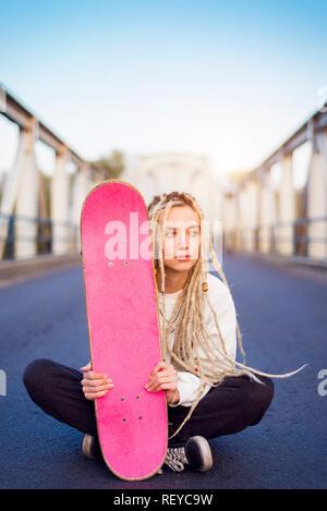 Junge Frau sitzt auf der Brücke mit Skate portrait - Stockfoto