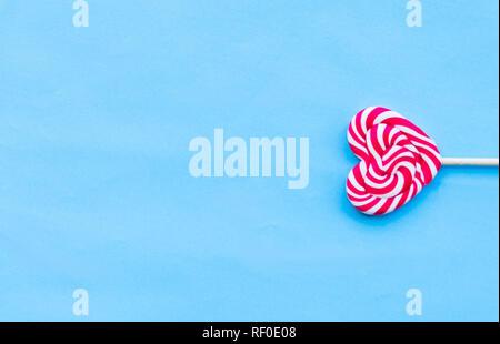 Single Valentines Tag herzförmigen Lollipop blauen Hintergrund. Liebe Konzept. Minimalismus. - Stockfoto