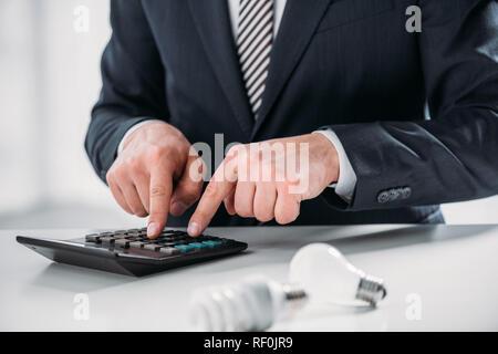 7/8-Ansicht der Geschäftsmann in mit Taschenrechner in der Nähe von Leuchtstofflampen auf weißem Hintergrund, Energieeffizienz Konzept - Stockfoto