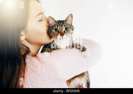 Junge Frau umarmen und küssen Katze auf weißem Hintergrund - Stockfoto