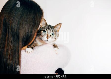 Junge Frau umarmen Katze auf weißem Hintergrund - Stockfoto