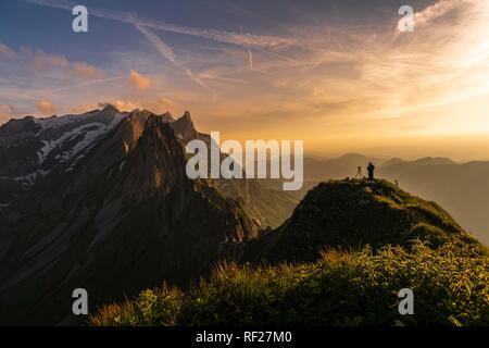 Fotograf auf grasigen Grat bei Sonnenuntergang mit Säntis Peak im Hintergrund, Wasserauen, Appenzell, Schweiz - Stockfoto