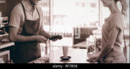 Kunde die Zahlung durch Zahlung terminal am Schalter - Stockfoto