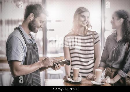 Kunde die Zahlung durch Zahlung terminal - Stockfoto