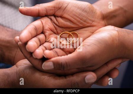 Der Mensch und seine Frau, die Hand mit Paar goldene Verlobungsringe - Stockfoto
