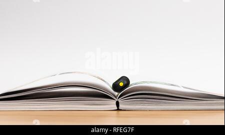 Buchen Sie mit fluoreszierenden Marker auf Schreibtisch aus Holz und weißen Hintergrund öffnen - Stockfoto