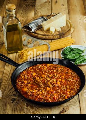 Foto eines pan der traditionellen Sauce Bolognese mit spaghetti Pasta, Olivenöl und Parmesan im Hintergrund. - Stockfoto