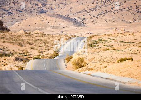 Kings Highway, schöne kurvenreiche Straße durch das Wadi Rum Wüste mit Hügeln in der Ferne in Jordanien. - Stockfoto