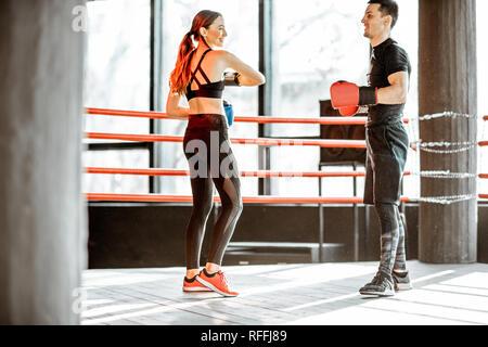 Junge Frau Training mit Personal Trainer auf den Boxring in der Turnhalle - Stockfoto