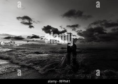 Silhouetten der Braut und Bräutigam am Strand bei Sonnenuntergang im Meer Wasser umarmen. Schwarzweiß gedreht - Stockfoto