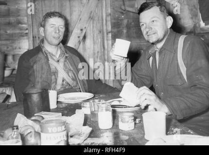 """Schwarz-weiß Foto von zwei unrasiert, Männer im mittleren Alter, jedem tragen wollene Shirts und Hosenträgern, sitzen gemeinsam in einer Blockhütte oder Shack, essen eine Mahlzeit in einem unordentlichen Tabelle, mit verschüttetem Zutaten, ein Glas Milch oder Zucker, und eine Dose """"Marke Pfirsiche York' im Vordergrund sichtbar, während einer Jagd und Angeln in Alaska, USA, 1955 entfernt fotografiert. () - Stockfoto"""